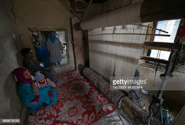 In this photograph taken on March 22 a Kashmiri weaver is watched by his family as he works works in silk and wool to make a carpet on a loom in a...