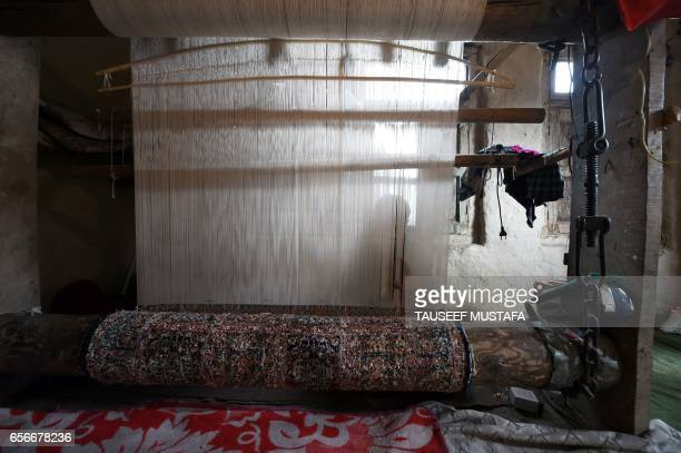 In this photograph taken on March 22 a Kashmiri weaver works in silk and wool to make a carpet on a loom in a traditionally constructed home on the...