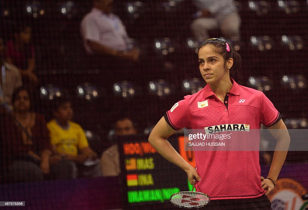 In this photograph taken on March 25, 2015, <a gi-track='captionPersonalityLinkClicked' href=/galleries/search?phrase=Saina+Nehwal&family=editorial&specificpeople=729912 ng-click='$event.stopPropagation()'>Saina Nehwal</a> of India reacts during her women's badminton singles match against Riay Mukherjee of India at the Yonex-Sunrise India Open 2015 at the Siri Fort Sports Complex in New Delhi. Badminton star <a gi-track='captionPersonalityLinkClicked' href=/galleries/search?phrase=Saina+Nehwal&family=editorial&specificpeople=729912 ng-click='$event.stopPropagation()'>Saina Nehwal</a> has shrugged off mounting pressure over whether she will become the first Indian woman ever to clinch the world number one ranking, at the Indian Open in New Delhi. Nehwal, currently number two after reaching the prestigious All-England Championship final this month, is expected to snatch the number one spot if she wins the tournament in front of a home crowd.