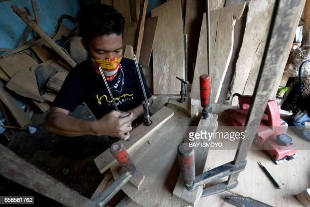 In this photograph taken on March 27 2017 guitar maker Ade begins the process of making a guitar body at a workshop in Jakarta Dana Suhana a graduate...