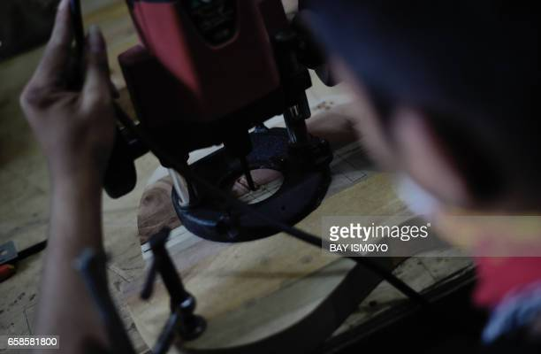 In this photograph taken on March 27 2017 guitar maker Ade cuts a guitar bridge hole at a workshop in Jakarta Dana Suhana a graduate in flight...