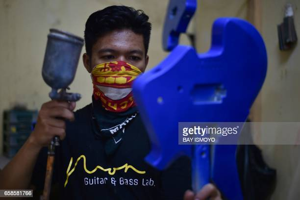 In this photograph taken on March 27 2017 guitar maker Ade spray paints the a guitar at a workshop in Jakarta Dana Suhana a graduate in flight...