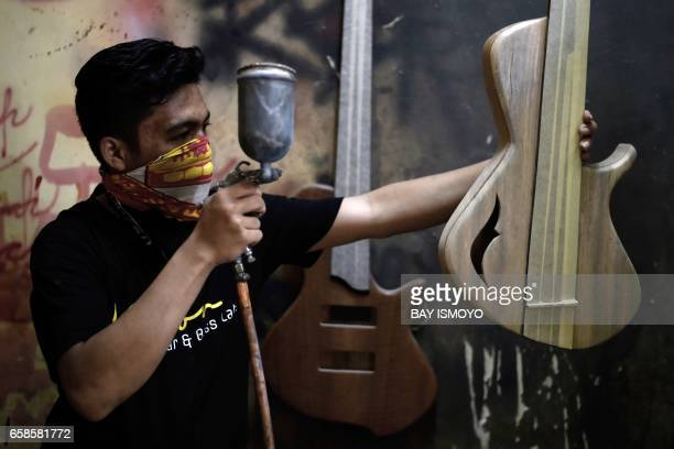 In this photograph taken on March 27 2017 guitar maker Ade sprays a base coat to a guitar before he paints it at a workshop in Jakarta Dana Suhana a...