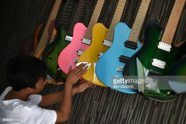 In this photograph taken on March 27 2017 guitar maker Hudri polishes finished guitars at a workshop in Jakarta Dana Suhana a graduate in flight...