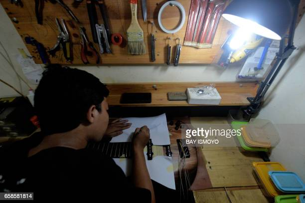 In this photograph taken on March 27 2017 guitar maker Jammy applies the finishing touches to a guitar at a workshop in Jakarta Dana Suhana a...