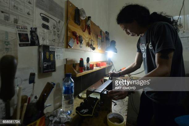 In this photograph taken on March 27 2017 guitar maker Rino applies finishing touches to a guitar at a workshop in Jakarta Dana Suhana a graduate in...