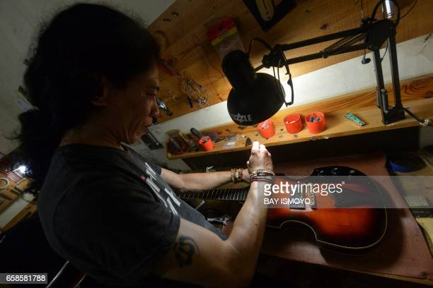 In this photograph taken on March 27 2017 guitar maker Rino applies the finishing touches to a guitar at a workshop in Jakarta Dana Suhana a graduate...