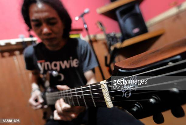 In this photograph taken on March 27 2017 guitar maker Rino checks a finished guitar at a workshop in Jakarta Dana Suhana a graduate in flight...
