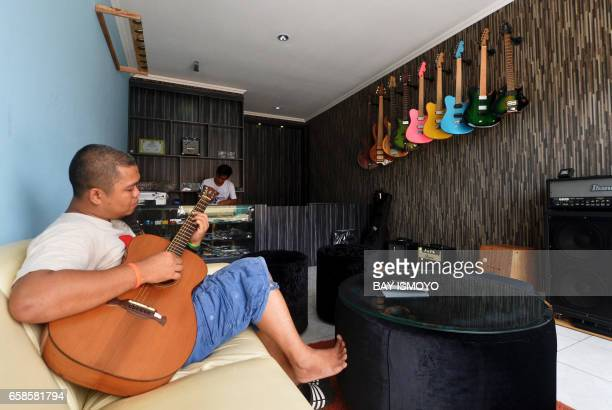 In this photograph taken on March 27 2017 guitar workshop owner Dana Suhana plays a guitar at his workshop in Jakarta Dana Suhana a graduate in...