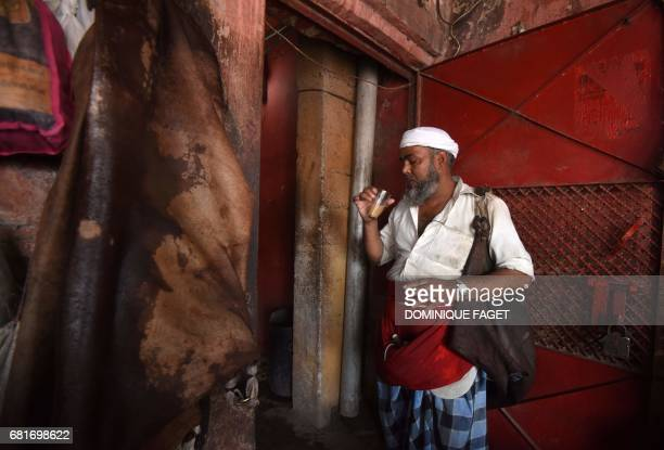 In this photograph taken on March 31 Indian water carrier Shakeel Ahmad drinks tea as he prepares to deliver water to a customer in New Delhi Shakeel...