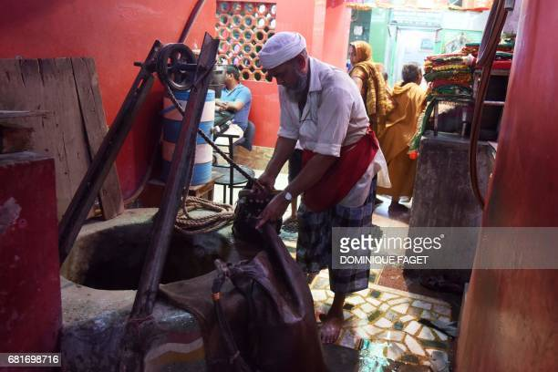In this photograph taken on March 31 Indian water carrier Shakeel Ahmad fills up a goat hide canteen from a well in New Delhi Shakeel Ahmad wanders...