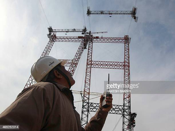 In this photograph taken on March 4 an Indian engineer gives instructions to a cable crane operator through a wireless set at the site of the...