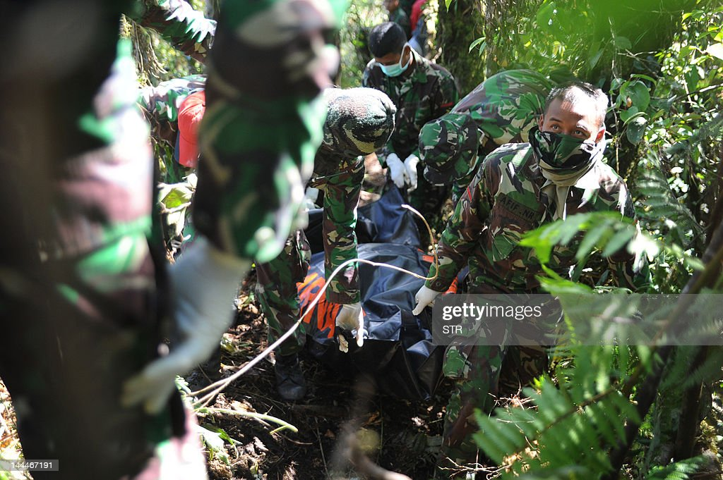In this photograph taken on May 12 2012 Indonesian soldiers recover bodies at the crash site of the Russian Sukhoi Superjet 100 in Mount Salak...