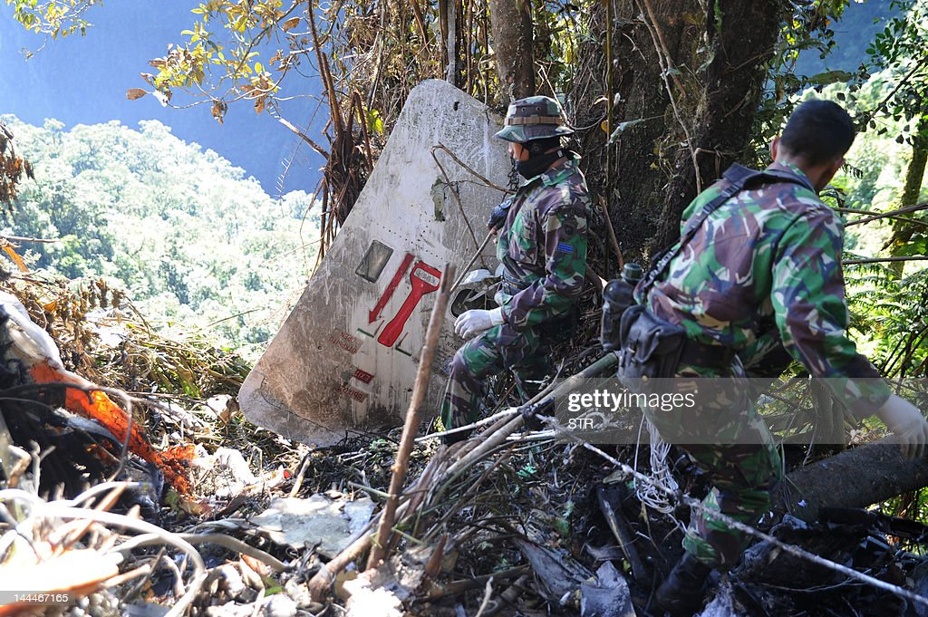 In this photograph taken on May 12 2012 Indonesian soldiers search the wreckage and debris for bodies of passengers and the flight recorder at the...
