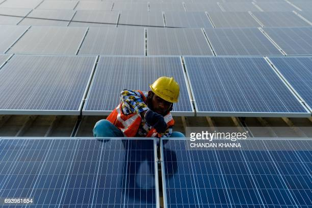 In this photograph taken on May 16 an Indian labourer installs solar panels at a site in Greater Noida some 45km east of the capital New Delhi Solar...