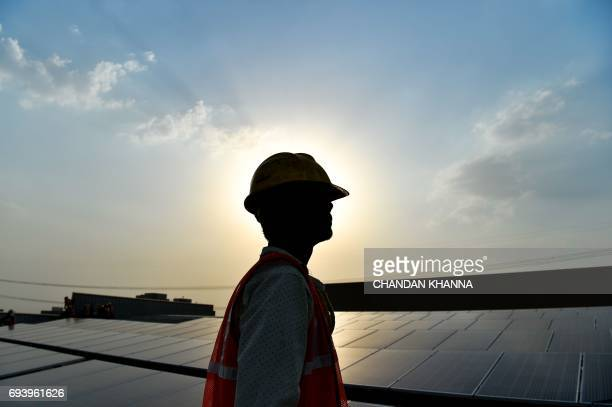 In this photograph taken on May 16 an Indian labourer looks on next to solar panels at a site in Greater Noida some 45km east of the capital New...
