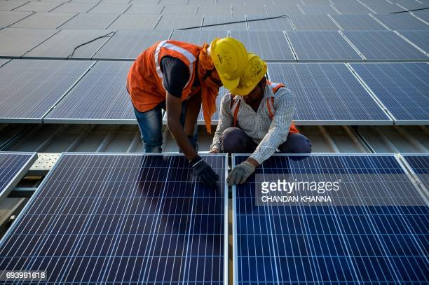In this photograph taken on May 16 Indian labourers install solar panels at a site in Greater Noida some 45km east of the capital New Delhi Solar...