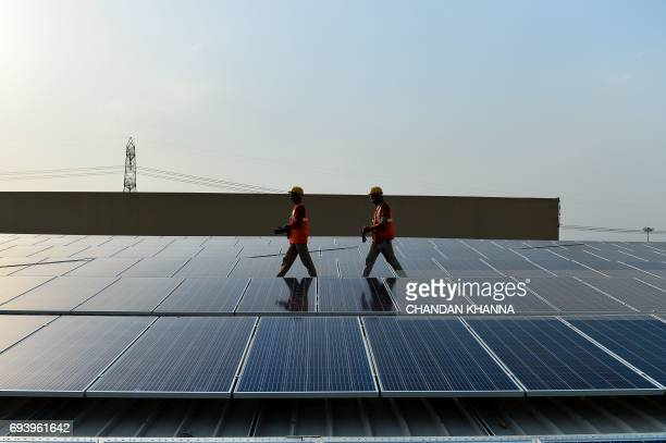 In this photograph taken on May 16 Indian labourers walk past solar panels at a site in Greater Noida some 45km east of the capital New Delhi Solar...