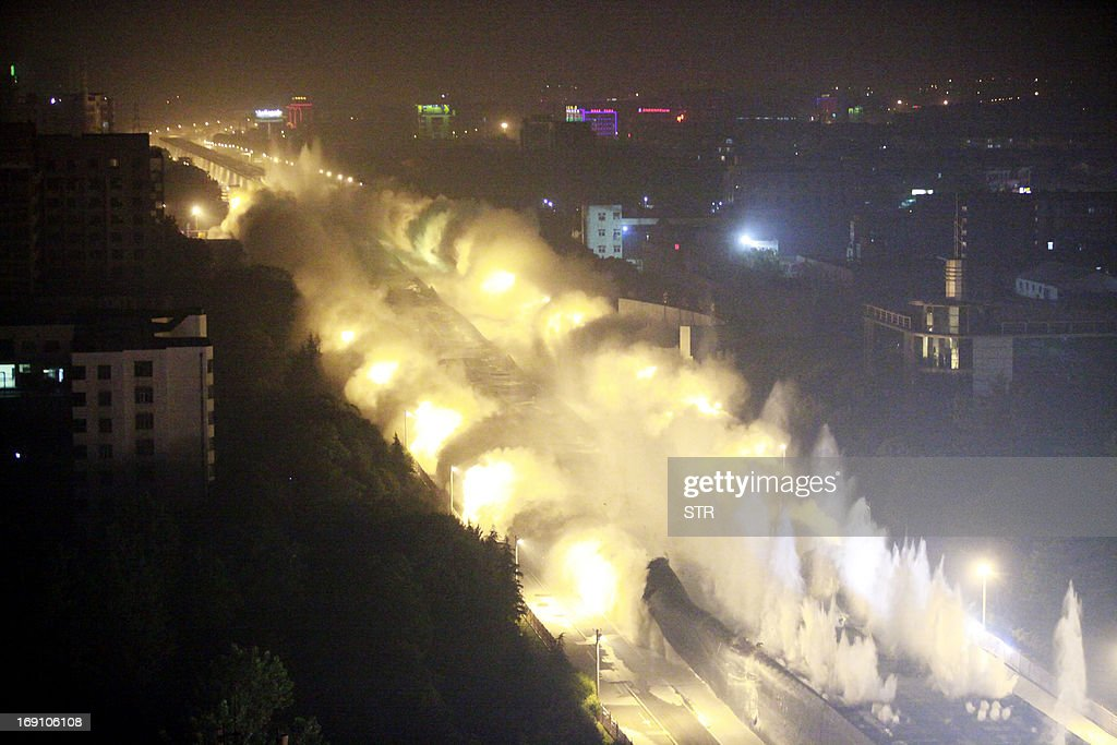 In this photograph taken on May 19, 2013, explosives go off as Dunyang highway viaduct collapses during a controlled demolition in Wuhan, central China's Hubei province. With 100,000 volt wiring running alongside the viaduct and 30 major gas pipelines underneath it, explosives experts were faced with a task requiring particular precision. The two mile long viaduct was the longest concrete bridge ever demolished in China, local media reported. CHINA OUT AFP PHOTO