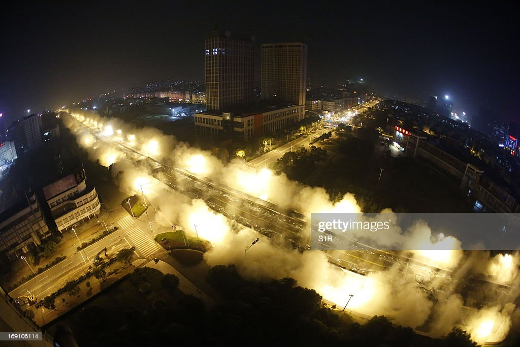 In this photograph taken on May 19, 2013, explosives go off as Dunyang highway viaduct collapses during a controlled demolition in Wuhan, central China's Hubei province. With 100,000 volt wiring running alongside the viaduct and 30 major gas pipelines underneath it, explosives experts were faced with a task requiring particular precision. The two mile long viaduct was the longest concrete bridge ever demolished in China, local media reported. CHINA