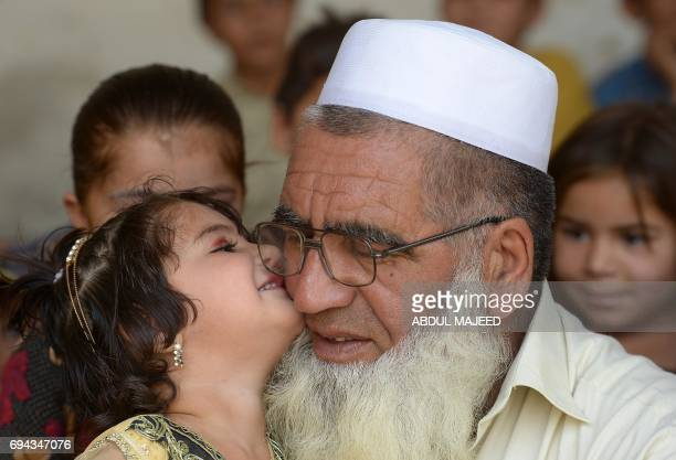 In this photograph taken on May 20 Pakistani father Gulzar Khan who has 36 children from his three wives receives a kiss from one of his daughters at...