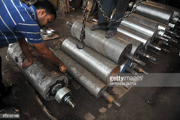 In this photograph taken on May 27 Indian labourers work at a lathe machinery workshop in Siliguri India on May 29 2015 reported economic growth of...