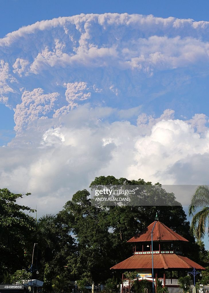 In this photograph taken on May 30 a giant cloud of ash and steam rise from erupting Sangeang Api volcano seen from Bima town on Sumbawa island...