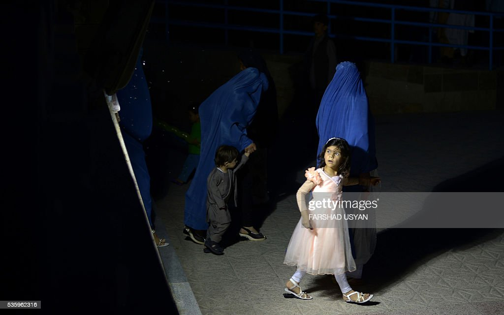 In this photograph taken on May 30, 2016, Afghan burqa-clad women lead children as they walk through a courtyard of Hazrat-e-Ali shrine, or Blue Mosque, in Mazar-i-Sharif. / AFP / FARSHAD