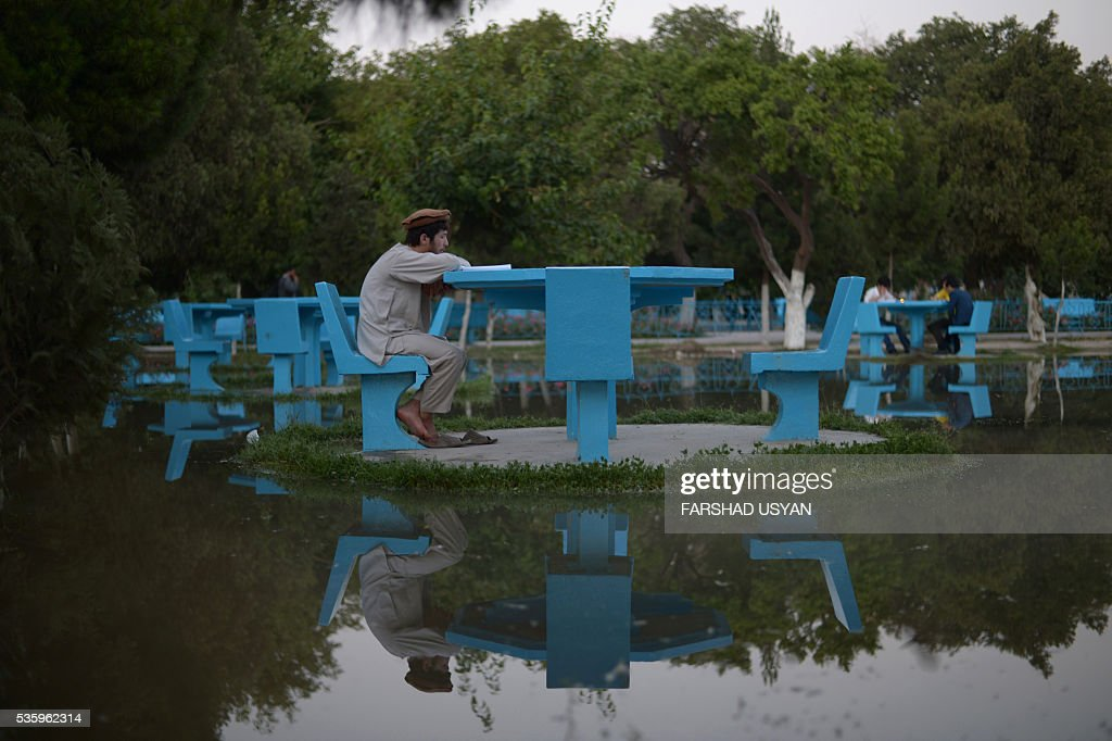 TOPSHOT In this photograph taken on May 30 an Afghan student reads a book in the courtyard of HazrateAli shrine or Blue Mosque in MazariSharif / AFP...