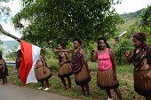 In this photograph taken on May 9 2015 Papuan women wearing traditional tribal costume and waving the Indonesian flag greet the motorcade of...