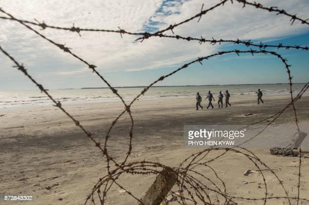 TOPSHOT In this photograph taken on November 12 Myanmar border police patrol the beach near a makeshift camp in Rakhine state in Myanmar where...