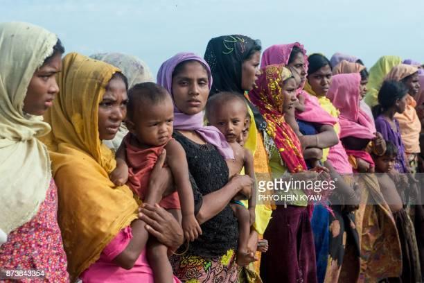 TOPSHOT In this photograph taken on November 12 women hold children at a makeshift camp in Rakhine state in Myanmar where hundreds of Rohingya...