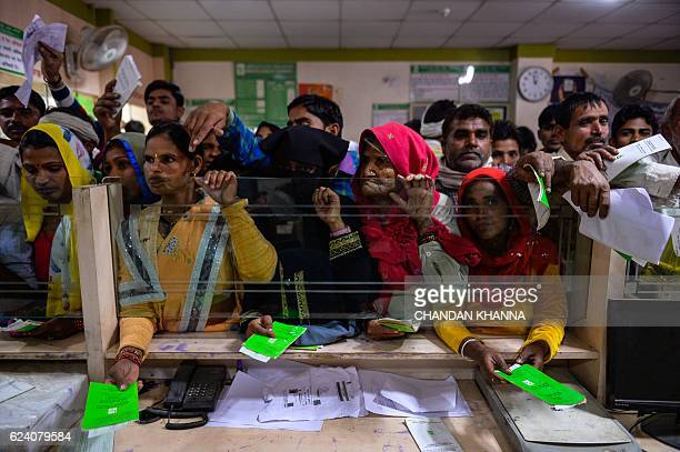 In this photograph taken on November 16 Indian villagers wait inside the bank to make the transactions in Basendua village in Bulandshahr in northern...