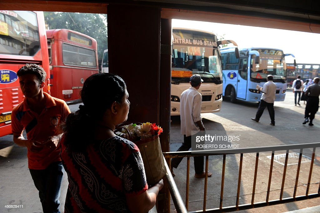 In this photograph taken on November 18, 2013, a Sri Lankan resident waits to take a six-hour ride back to her home at a bus terminal in Colombo. The mother of three was returning to her hometown of Hambantota in southern Sri Lanka after attending the wedding of her eldest daughter in the country's capital Colombo. The plastic flower arrangement she is carrying was a momento kept from the wedding ceremony. AFP PHOTO/Roberto SCHMIDT
