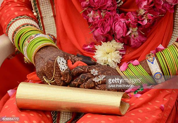 In this photograph taken on November 20 an Indian bride waits ahead of the start of a mass wedding ceremony in Ahmedabad Mass wedding ceremonies are...