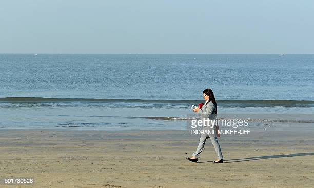In this photograph taken on November 20 an Indian woman walks on Juhu beach in Mumbai India published new guidelines for webbased ridehailing firms...