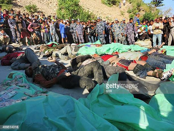 In this photograph taken on November 22 2014 Nepalese bystanders look at the bodies of victims recovered after a bus ploughed into the Bheri river in...