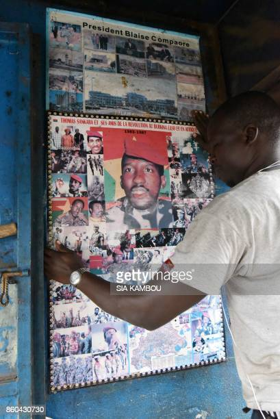 In this photograph taken on October 11 an admirer of former Burkina Faso President Thomas Sankara fixes a poster featuring images of the former...