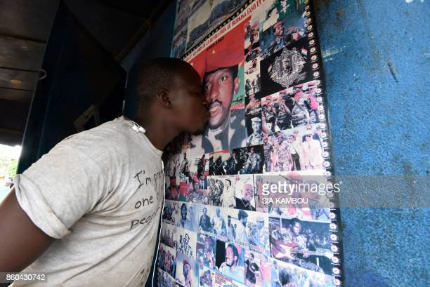 TOPSHOT In this photograph taken on October 11 an admirer of former Burkina Faso President Thomas Sankara kisses a poster featuring images of the...