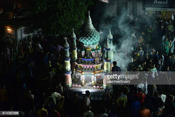 In this photograph taken on October 12 Indian Muslims throng around a colourful Tazia during a procession to mark Ashura in Ahmedabad Devout Shiite...