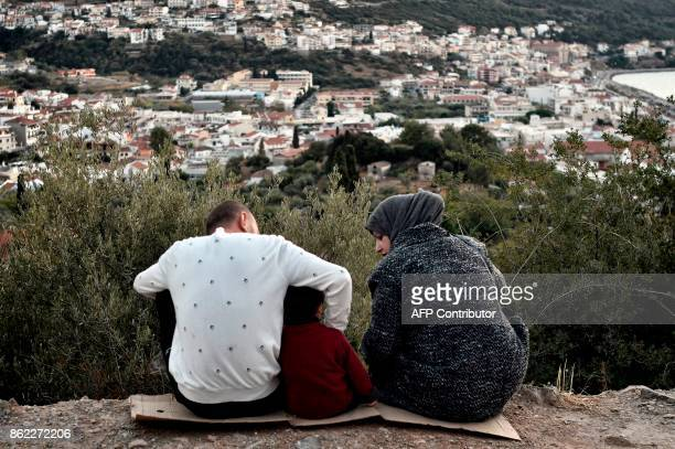 In this photograph taken on October 13 a family sit on a hill overlooking the town on the Greek island of Samos Nearly 300 Syrians Iraqis Afghans and...
