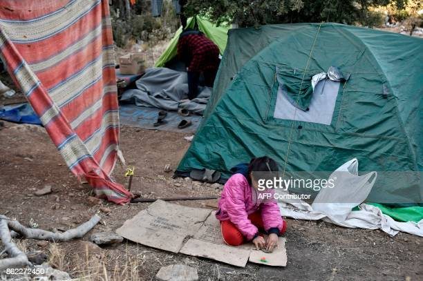 In this photograph taken on October 13 a young Iraqi refugee the unnamed daughter of Saura sits by their shelter in woods on the Greek island of...
