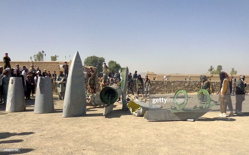 In this photograph taken on October 13 Afghan Taliban militants gather around parts of a US F16 aircraft that was struck over in Sayid Karam district...