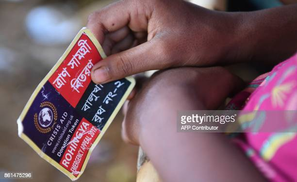 In this photograph taken on October 14 2017 a Rohingya refugee holds her token to collect aid at the Balukhali refugee camp in the Bangladeshi...