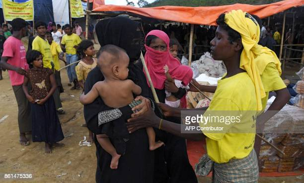 In this photograph taken on October 14 2017 a volunteer blocks a Rohingya refugee from collecting aid after she came back a third time at the...