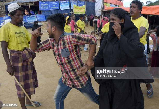 In this photograph taken on October 14 2017 a volunteer escorts off a Rohingya refugee from collecting aid after she came back a second time at the...