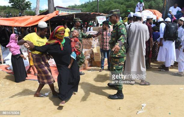 In this photograph taken on October 14 2017 a volunteer pulls out a Rohingya refugee from a queue to collect aid after she came back a second time at...