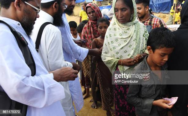 In this photograph taken on October 14 2017 Bangladeshi members of an NGO distribute money among Rohingya refugees collecting aid at the Balukhali...