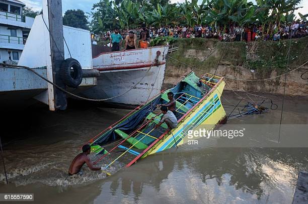 In this photograph taken on October 18 2016 rescue workers are seen on the sunken ferry partially lifted from the water near the river bank The death...