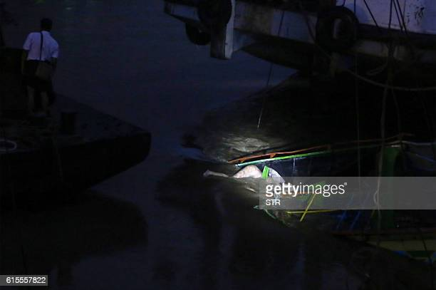 TOPSHOT In this photograph taken on October 18 a body floats on the sunken ferry partially lifted from the water near the river's bank The death toll...